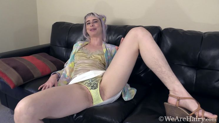 Esme strips naked on her black couch